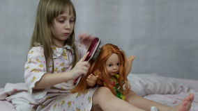 Girl playing with doll sitting on the bed stock video