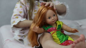 Girl playing with doll sitting on the bed stock footage