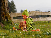 Girl playing with a doll. Girl sitting in the garden and playing with a doll Stock Photography