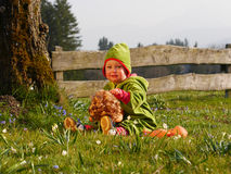 Girl playing with a doll. Girl sitting in the garden and playing with a doll Royalty Free Stock Images