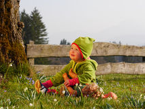 Girl playing with a doll. Girl sitting in the garden and playing with a doll Royalty Free Stock Image