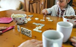 Girl playing domino with her family Royalty Free Stock Photo