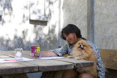 Girl playing and drawing color pen on white paper with holding h. Er pomeranian dog relaxing at home royalty free stock images