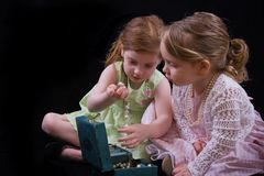 Girl playing dress-up. Two little girls playing with costume jewelry Stock Image