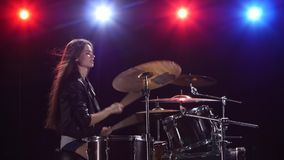 Girl is playing the drums. Black background. Red blue light from behind. Side view. Girl at a rock concert is playing drums. Black background. Red blue light stock video