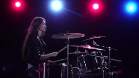Girl is playing the drums. Black background. Red blue light from behind. Side view. Slow motion. Girl at a rock concert is playing drums. Black background. Red stock footage