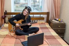 Girl playing electric guitar sitting on the bed. In the bedroom stock photography