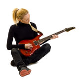 Girl playing an electric guitar sitting down stock photography