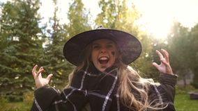 Girl playing evil witch, angrily roaring at camera, Halloween party celebration. Stock photo stock image