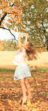 Girl playing with fallen leaves. Kid - barefoot girl playing with fallen leaves and throwing it on autumn Royalty Free Stock Images