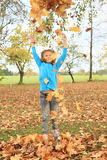 Girl playing with fallen leaves Stock Photo