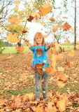 Girl playing with fallen leaves Royalty Free Stock Image