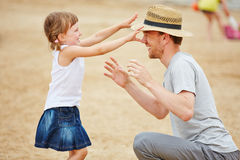 Girl playing with father on beach Royalty Free Stock Images