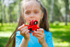 Girl playing with a fidget spinner stock images