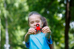 Girl playing with a fidget spinner Royalty Free Stock Photography