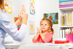 Girl playing finger games with teacher Stock Photography