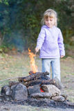 Girl playing with fire on natural background Royalty Free Stock Image