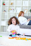 Girl playing on floor in living room Stock Images