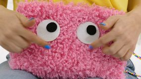 Girl playing with a fluffy bag. Cheerful fluffy bag cosmetic bag in female hands stock video footage