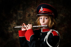 Girl playing a flute. Twelve year old girl wearing a marching band uniform playing her flute Royalty Free Stock Photo