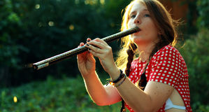 Girl playing at the flute Stock Images