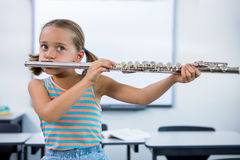Girl playing flute in classroom Royalty Free Stock Images