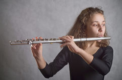 Girl Playing Flute. On a gray background Stock Photo