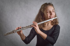 Girl Playing Flute. On a gray background Royalty Free Stock Photo