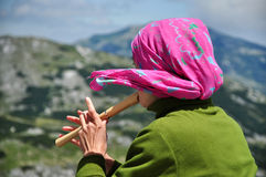 Girl playing on flute in the mountains Royalty Free Stock Photo