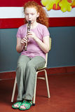 Girl playing flute in music lessons Royalty Free Stock Images
