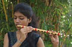 A girl playing flute. A teenage Indian girl playing a flute in a bamboo forest Royalty Free Stock Photo
