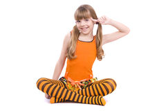 Girl is playing the fool. You are fool. Little girl in the orange dress with finger near her head is sitting on the floor. Portrait of an attractive young stock photos