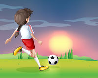 A girl playing football in the afternoon Stock Image