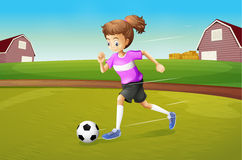 A girl playing football at the farm Royalty Free Stock Photography