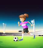 A girl playing football at the field Royalty Free Stock Images