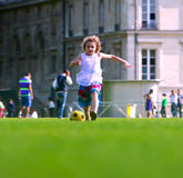 Girl playing football in front the school building Stock Photos