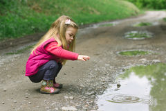 Girl playing in forest. Little blonde girl playing in forest, natural background - throwing rocks into water Stock Photo