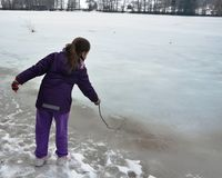 Girl Playing on a Frozen Lake. Girl standing on the edge of a frozen lake playing with a branch Royalty Free Stock Photo