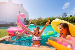 Girl playing games with friends during pool party. Excited teenage girl holding her hands up, playing games with friends during outdoor pool party in summer stock photography