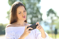 Girl playing games on the smart phone Royalty Free Stock Image