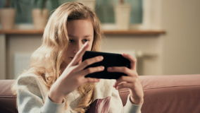 Girl playing games on smartphone. Leisure activity at home after school stock video