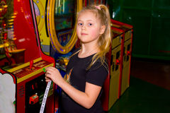 Girl playing gaming machines. Little girl playing on the slot machines and win prize tokens Stock Image