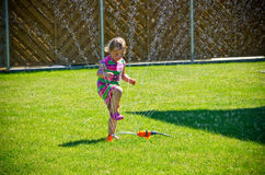 Girl playing with a garden sprinkler Stock Photos