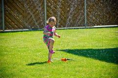 Girl playing with a garden sprinkler Stock Photos