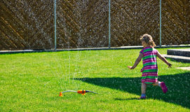 Girl playing with a garden sprinkler Stock Image