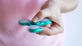 Girl playing with a glossy light colourful hand fidget spinner toy stock footage