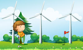 A girl playing golf near the windmills Stock Images