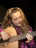 Girl playing guitar. Portrait of young girl playing acoustic guitar, isolated on black background Royalty Free Stock Images