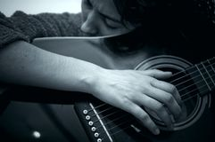 Girl Playing Guitar. Black and white closeup portrait of a woman playing guitar.  Horizontal format Stock Photo