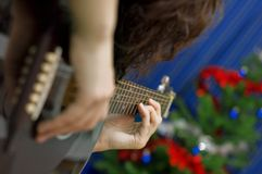 Girl Playing Guitar. Girl playing at guitar with a Christmas tree in the background (focus at second hand Royalty Free Stock Photos